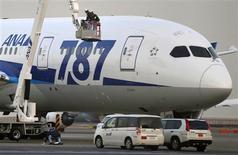 """Boeing informó el miércoles de un descenso interanual en sus ganancias del cuarto trimestre, aunque superaron las expectativas del mercado, y dijo que sus previsiones para 2013 no esperan un """"impacto financiero significativo"""" de la suspensión de los vuelos de su 787 Dreamliner tras una serie de incidentes. Imagen de unos mecánicos trabajando junto a un Dreamliner de All Nippon Airways (ANA) en el aeropuerto de Haneda en Tokio el 16 de enero. REUTERS/Toru Hanai/Archivos"""
