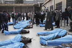 Parentes caminham por entre os corpos de vítimas de um massacre em Aleppo, na Síria. A imprensa estatal síria responsabilizou os rebeldes islâmicos da Frente Nusra pela morte de dezenas de pessoas em Aleppo (norte), contradizendo relatos de ativistas que atribuíram o massacre às forças do presidente Bashar al Assad. 29/01/2013 REUTERS/Zain Karam