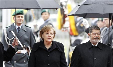 German Chancellor Angela Merkel and Egyptian President Mohamed Mursi inspect the guard of honour during a welcome ceremony before talks in Berlin January 30, 2013. Mursi flew to Germany on Wednesday to try to convince Europe of his democratic credentials, leaving behind a country in crisis after a week of violence that has killed more than 50 people. REUTERS/Tobias Schwarz (GERMANY - Tags: POLITICS)
