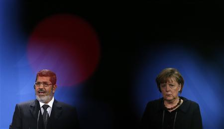 German Chancellor Angela Merkel and Egyptian President Mohamed Mursi address the media following their talks in Berlin January 30, 2013. German Chancellor Angela Merkel urged Egypt's Islamist president on Wednesday to open a dialogue with all political forces in the crisis-ridden Arab country after a week of violence that has killed more than 50 people. REUTERS/Tobias Schwarz