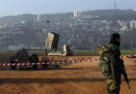 An Israeli soldier stands guard next to an Iron Dome rocket interceptor battery deployed near the northern Israeli city of Haifa January 28, 2013