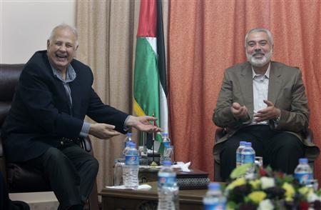 Hamas prime minister Ismail Haniyeh (R) gestures during a meeting with Hanna Nasir (L), chairman of the Palestinian Central Election Commission (CEC), in Gaza City January 30, 2013. REUTERS/Ahmed Zakot