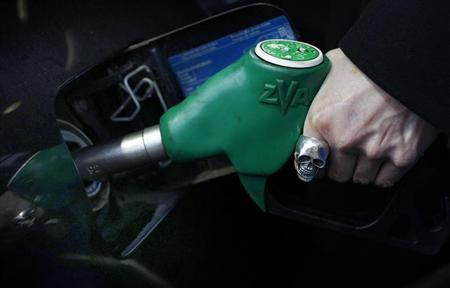 A woman fuels her car at a petrol station in London January 3, 2011. REUTERS/Suzanne Plunkett