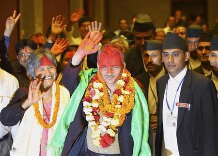 Nepal Prime Minister Dr. Baburam Bhattarai (C) waves with his wife Hisila Yami as they walk out from Parliament in Kathmandu August 28, 2011.REUTERS/Navesh Chitrakar/Files