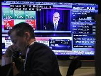 Traders work on the floor of the New York Stock Exchange while a screen shows U.S. Federal Reserve Chairman Ben Bernanke's news conference, December 12, 2012