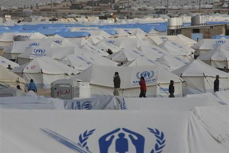 Syrian refugees walk along tents at the Al Zaatri Syrian refugee camp in the Jordanian city of Mafraq, near the border with Syria January 30, 2013.Donor countries have pledged more than $1.5 billion to aid Syrians stricken by civil war, U.N. Secretary-General Ban Ki-moon said on Wednesday after warning that the conflict had wrought a catastrophic humanitarian crisis. REUTERS/Majed Jaber (JORDAN - Tags: POLITICS CIVIL UNREST)