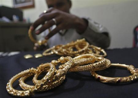A goldsmith holds finished gold bangles at a workshop in Kolkata January 16, 2013. REUTERS/Rupak De Chowdhur