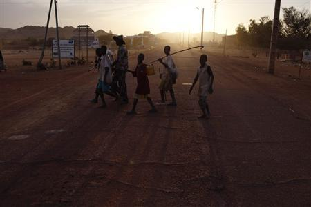Boys cross the street in the recently liberated town of Douentza, Mali January 29, 2013. REUTERS/Joe Penney