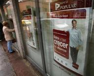 Banco Popular anunció el miércoles el nombramiento de Francisco Gómez Martín, hasta ahora su director general de riesgos, como consejero delegado de la entidad con plenas funciones ejecutivas. En la imagen de archivo, una mujer saca dinero de un cajero en un Banco Popular en Madrid en septiembre de 2012. REUTERS/Sergio Perez