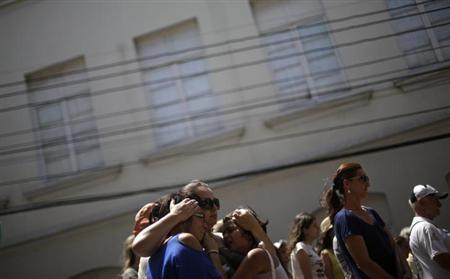 People react as they stand next to Boate Kiss nightclub in the southern city of Santa Maria, 187 miles (301 km) west of the state capital Porto Alegre, January 29, 2013. REUTERS/ Ricardo Moraes