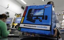 Um cliente carrega a caixa de um computador após comprá-lo em um supermercado em São Paulo. Os supermercados brasileiros devem apurar neste ano uma desaceleração no ritmo de crescimento de vendas em relação a 2012, diante de perspectivas mais conservadoras para a economia do país e estabelecendo um patamar de acomodação para o setor. 3/03/2011 REUTERS/Nacho Doce