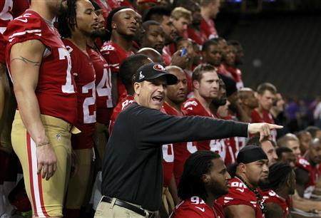 San Francisco 49ers head coach Jim Harbaugh directs his players into position for their team picture during Media Day for the NFL's Super Bowl XLVII in New Orleans, Louisiana January 29, 2013. The 49ers will meet the Baltimore Ravens in the game on February 3. REUTERS/Joe Skipper
