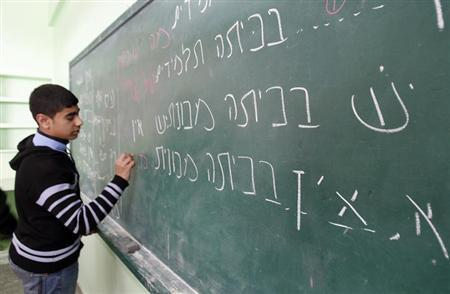 A Palestinian ninth grade student writes on the blackboard during a Hebrew class at a Gaza school in Gaza City January 28, 2013. REUTERS/Ahmed Zakot