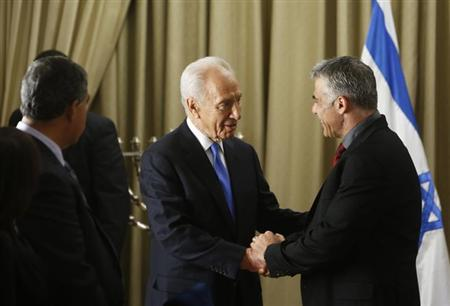 Israel's President Shimon Peres (C) shakes hands with Yair Lapid, leader of the Yesh Atid (There's a Future) party, in Jerusalem January 30, 2013, after receiving the official results of the general elections held on January 22. REUTERS/Ronen Zvulun