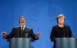 Las autoridades de una ciudad egipcia redujeron el toque de queda impuesto por el presidente Mohamed Mursi, mientras el líder islamista reducía el miércoles una visita a Europa para abordar la oleada de violencia que ha sufrido al país desde que asumió el poder hace siete meses. En la imagen, el presidente egipcio, Mohamed Mursi (a la izquierda) y la canciller alemana, Angela Merkel, en una rueda de prensa en la cancillería de Berlín, el 30 de enero de 2013. REUTERS/Fabrizio Bensch