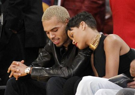 Recording artist Rihanna leans her head on Chris Brown as they sit together courtside at the NBA basketball game between the New York Knicks and Los Angeles Lakers in Los Angeles December 25, 2012. REUTERS/Danny Moloshok
