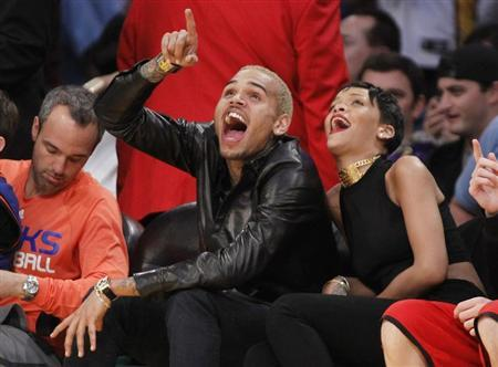 Recording artists Chris Brown (L) and Rihanna laugh as they sit together courtside at the NBA basketball game between the New York Knicks and Los Angeles Lakers in Los Angeles December 25, 2012. REUTERS/Danny Moloshok