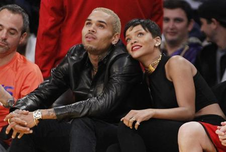 Recording artist Rihanna (R) leans her head on Chris Brown as they sit together at the NBA basketball game between the New York Knicks and Los Angeles Lakers in Los Angeles December 25, 2012. REUTERS/Danny Moloshok