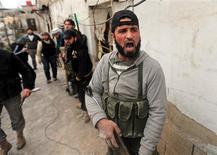 """Aviones de guerra israelíes atacaron un centro de investigación en la provincia de Damasco al amanecer del miércoles, informó el miércoles el mando militar sirio, negando noticias de que las naves habían impactado un convoy que transportaba armas desde el país a Líbano. En la imagen, un combatiente del Ejército Libre de Siria grita """"Allahu Ajbar"""" (""""Alá es grande"""") durante combates en el barrio Ain Tarma de Damasco, el 30 de enero de 2013. REUTERS/Goran Tomasevic"""