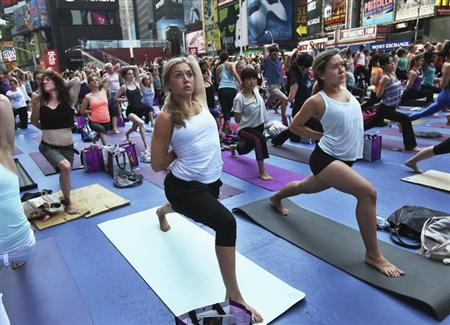 People practice yoga on the morning of the summer solstice in New York's Times Square June 20, 2012. REUTERS/Shannon Stapleton