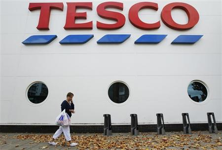 A shopper passes a Tesco supermarket in London October 5, 2011. REUTERS/Luke MacGregor
