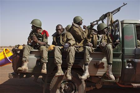 Malian soldiers heading to Gao in a pickup truck arrive in the recently liberated town of Douentza January 30, 2013. French troops took control on Wednesday of the airport of Mali's northeast town of Kidal, the last urban stronghold held by Islamist rebels, as they moved to wrap up the first phase of a military operation to wrest northern Mali from rebel hands. REUTERS/Joe Penney (MALI - Tags: CIVIL UNREST POLITICS MILITARY CONFLICT)