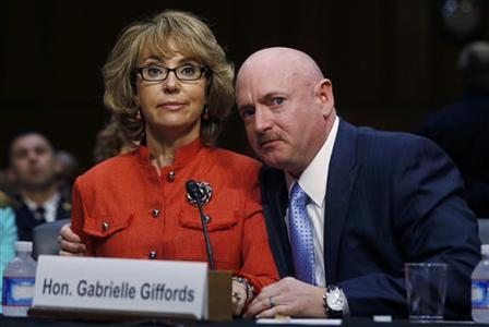 Former U.S. Rep. Gabrielle Giffords (L) delivers her opening remarks while seated next to her husband, former U.S. Navy Captain Mark Kelly, during a hearing held by the Senate Judiciary committee about guns and violence on Capitol Hill in Washington, January 30, 2013. REUTERS/Larry Downing