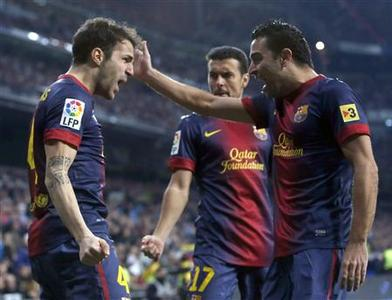 Barcelona's Cesc Fabregas (L) celebrates scoring a goal against Real Madrid with teammates Xavi Hernandez (R) and Pedro Rodriguez during their Spanish King's Cup semi final first leg soccer match at Santiago Bernalbeu stadium in Madrid January 30, 2013. REUTERS/Juan Medina