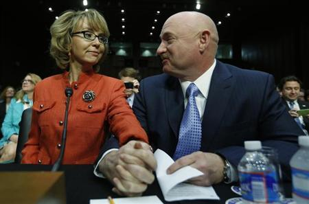 Former U.S. Rep. Gabrielle Giffords sits with her husband, U.S Navy Captain Mark Kelly, prior to delivering a statement at a Senate Judiciary Committee hearing on gun violence, on Capitol Hill in Washington January 30, 2013. REUTERS/Kevin Lamarque