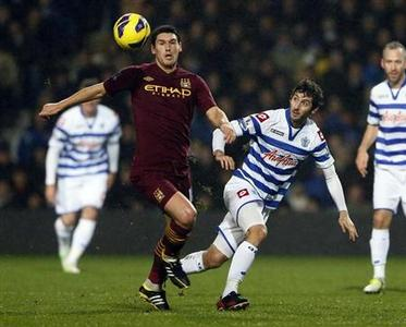 Manchester City's Gareth Barry (L) challenges Queen's Park Rangers' Estaban Granero during their English Premier League soccer match at Loftus Road Stadium in London January 29, 2013. REUTERS/Stefan Wermuth