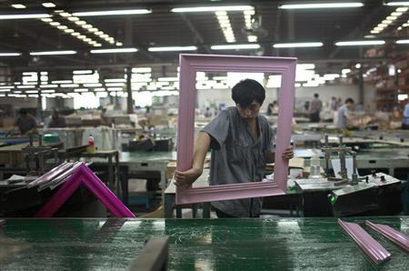 A worker picks up a photo frame as he operates on a photo and mirror frame assembly line at a factory in Zibo, Shandong Province May 28, 2012. REUTERS/Aly Song