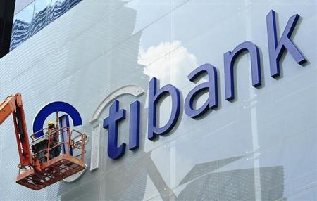 Construction workers install Citibank's neon sign on its Singapore main office at the central business district November 29, 2011. REUTERS/Harry Suhartono/Files