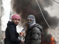 Free Syrian Army fighter look back as they stand in front of a burning barricade during heavy fighting in the Ain Tarma neighbourhood of Damascus January 30, 2013. REUTERS/Goran Tomasevic