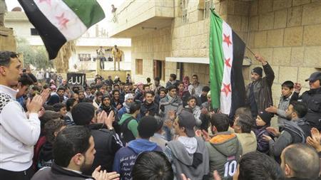 Demonstrators wave Syrian opposition flags during a protest against Syria's President Bashar al-Assad, in Al-Balad district, Deraa, in this picture provided by Shaam News Network and taken January 11, 2013. REUTERS/Ali Abu Salah/Shaam News Network/Handout
