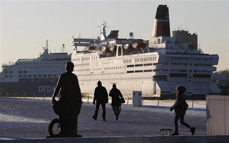 Pedestrians walk past cruise ships docked in the harbour in Oslo December 11, 2012. REUTERS/Suzanne Plunkett