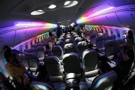 Journalists take pictures of the economy class cabin of the Boeing 787 Dreamliner as it is lit with rainbow colored LED lighting during a media tour of the aircraft in Singapore in this February 12, 2012 file photograph. REUTERS/Edgar Su/Files