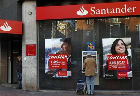 A man uses an ATM machine as another talks on the phone outside a Santander bank branch in Madrid January 31, 2013. Spain's Santander has sharply raised provisions against bad loans after defaults rose in its home market and key earnings-driver Brazil, while writedowns on rotten Spanish real estate also contributed to a 59 drop in yearly net profit. REUTERS/Susana Vera (SPAIN - Tags: BUSINESS REAL ESTATE)