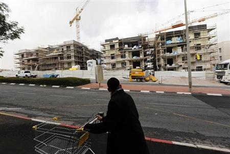 An ultra-Orthodox Jewish man pushes a shopping cart past a construction site in Gilo, a Jewish settlement that Israel erected on land it captured in the West Bank in a 1967 war and annexed unilaterally as part of its declared capital Jerusalem December 20, 2012. REUTERS/Ronen Zvulun/Files