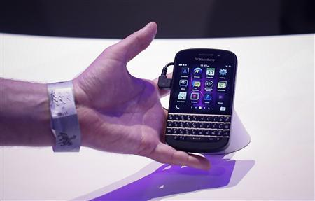 An attendee reaches out to grab a newly launched Research in Motion (RIM) Blackberry 10 device in New York January 30, 2013. REUTERS/Shannon Stapleton