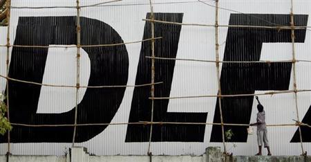 A man paints a logo of Indian property developer DLF Ltd. at their construction site in Mumbai June 11, 2007. REUTERS/Punit Paranjpe/Files