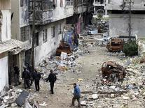 Free Syrian Army fighters walk past burnt vehicles as they enter a building in Homs January 30, 2013. REUTERS/Yazan Homsy