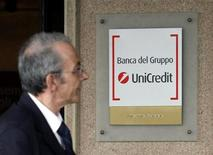 Мужчина смотрит на вывеску Unicredit, направляясь на собрание акционеров банка в Риме 14 ноября 2008 года. Крупнейший по величине активов банк Италии UniCredit до конца апреля 2013 года может продать свое подразделение в Казахстане АТФ-банк казахскому страховому холдингу Казнитрогенгаз (КНГ) за почти $500 миллионов, сообщили Рейтер источник, близкий к сделке, а также источник в банке. REUTERS/Giampiero Sposito