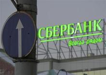 Уличный знак на фоне рекламы Сбербанка во Владивостоке 5 декабря 2012 года. Российский фондовый рынок снижается в конце месяца на фоне фиксации прибыли игроками после неплохого роста, но неиссякаемый спрос на акции Сбербанка удерживает индексы от провала. REUTERS/Sergei Karpukhin