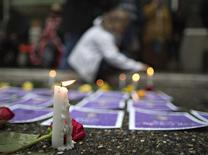 A supporter lights candles surrounding photos of murdered women outside the Missing Women's Commission of Inquiry being made public in Vancouver, British Columbia in this December 17, 2012, file photo. REUTERS/Andy Clark/Files