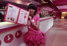A waitress poses with a menu during the media preview of a Barbie-themed cafe in Taipei January 30, 2013. REUTERS/Pichi Chuang