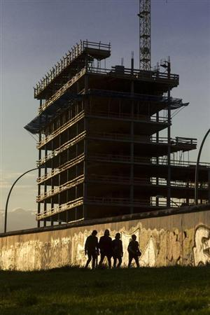 People walk at sunset past a section of the former Berlin Wall near a construction site in Berlin July 21, 2012. REUTERS/Thomas Peter (GERMANY - Tags: BUSINESS CONSTRUCTION)