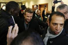 Pessoas tiram fotos do jogador David Beckham (C), rodeado por seguranças, depois de exame médico no hospital Pitie-Salpetriere, em Paris. 31/01/2013 REUTERS/Charles Platiau