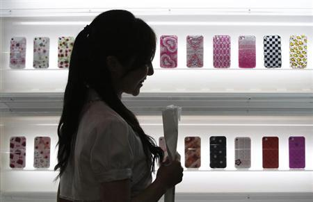 A woman waits for visitors in front of a smartphone accessories booth at Wireless Japan 2012, a smartphone and mobile phone technology exhibition, in Tokyo May 31, 2012. REUTERS/Issei Kato/Files