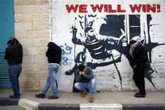 Palestinos que atiravam pedras protegem-se do gás lacrimogêneo lançado por forças de segurança israelenses durante confrontos em campo de refugiados em Belém, na Cisjordânia. Palestinos saudaram um relatório do Conselho de Direitos Humanos da ONU altamente crítico aos assentamentos judaicos na Cisjordânia ocupada, dizendo que isso justificava sua luta contra Israel. 24/01/2013 REUTERS/Ammar Awad
