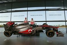 Los pilotos de la escudería McLaren de Fórmula Uno Jenson Button (a la izquierda en la imagen) y Sergio Pérez posan junto al nuevo monoplaza MP4-28 en la casa matriz de la firma en Woking, Inglaterra, ene 31 2013. La escudería McLaren presentó el jueves su monoplaza para el 2013 con un recuerdo al pasado, en una temporada en la que celebra 50 años disputando grandes premios y en la que tiene ganas de volver a lo más alto de la Fórmula Uno. REUTERS/Stefan Wermuth
